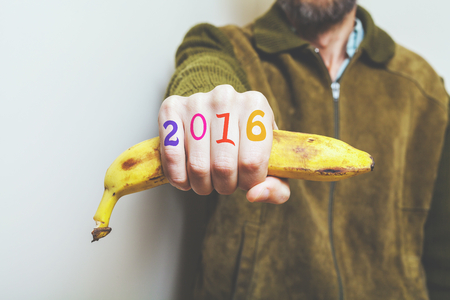 Man in  green jacket holding a banana in his fist, symbol of a monkey year. Figures 2016 painted on fingers. Stock Photo