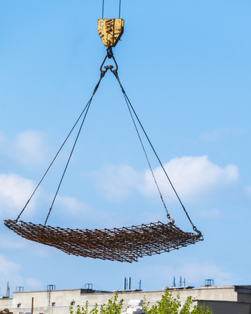 Construction of multi-storey brick building. A crane lowers the load against the blue sky Stock Photo