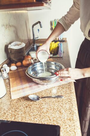 kitchen countertops: Woman on kitchen pours into a metal bowl of yogurt Stock Photo