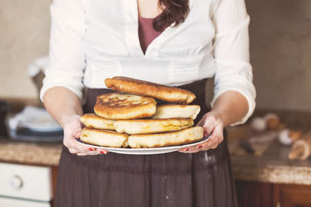 mouthwatering: A woman in a skirt holding a plate with a big mouth-watering fried pies Stock Photo