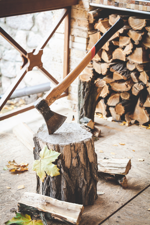 long handled: Long-handled ax sticking in a tree stump split piece of wood lying beside