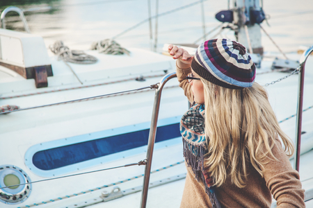 Young blond woman with long hair sitting on a yacht and looking into the distance