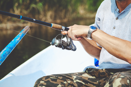 Hands fisherman keep spinning rod and rotate the handle fast-response spool close-up Stock Photo