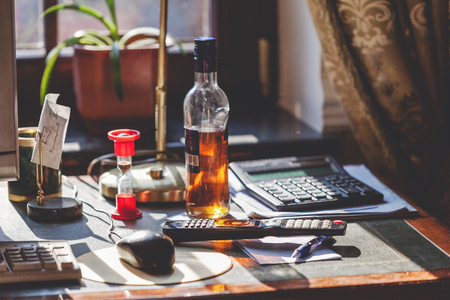 started strong alcohol bottle and hourglass stand on the desktop in the office in sunlight. Near calculator and remote control