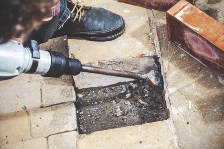 martillo de la construcción con una lanza larga y plana destruye escalones de ladrillo fuera de un día de verano. De cerca
