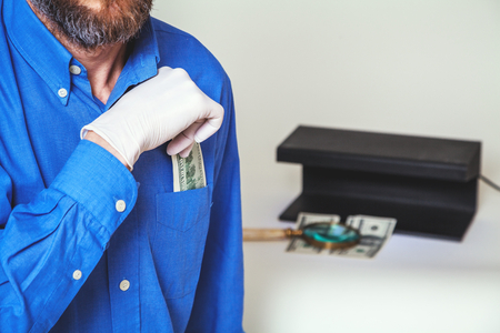 breast pocket: man with a beard in a blue shirt pulls from his breast pocket a dollar bill