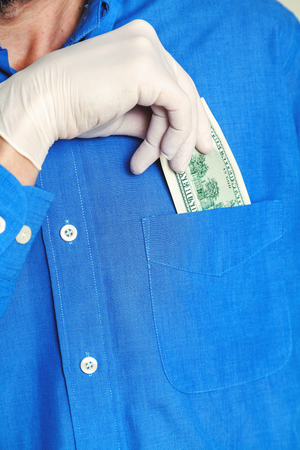 breast pocket: Hand in rubber glove hides in the breast pocket of a blue uniform shirt dollar bill. Close-up