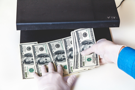 authenticate: Hands in rubber gloves authenticate dollar bills with a detector
