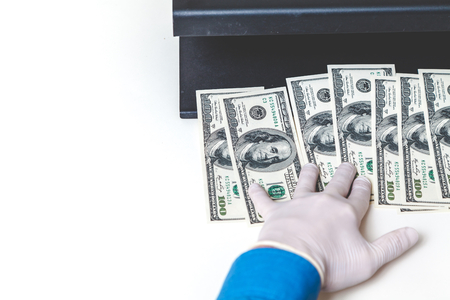 remuneraci�n: Hands in rubber gloves authenticate dollar bills with a detector