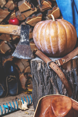 Autumn Still Life. Big ripe pumpkin lies on a stump beside the ax leather hat and belt. On stacked chopped wood background