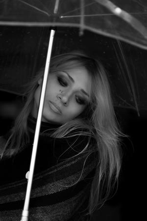 長いブロンドの髪を持つ美少女の肖像画。モデルは、スタイリッシュな透明傘の下で頭を下げました。モノクロ画像