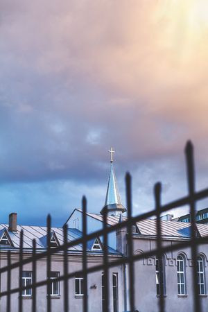 spire of the Catholic church with a cross on a background of cloudy sky. In the foreground lattice metal fence