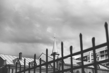 metal monochrome: Monochrome image of spire of the Catholic church with a cross on a background of cloudy sky. In the foreground lattice metal fence