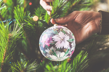 decorate: decorate the Christmas tree. men hands hang a glass bowl with a beautiful pattern on a green Christmas tree branch Stock Photo