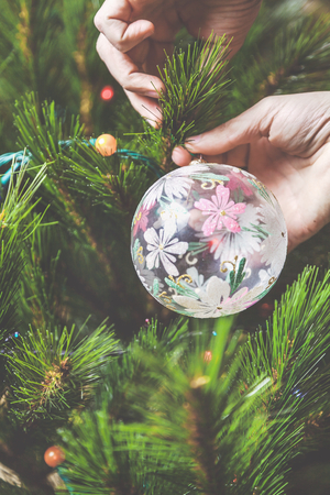 decorate the Christmas tree. men hands hang a glass bowl with a beautiful pattern on a green Christmas tree branch Stock Photo