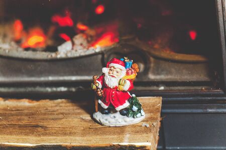 yule log: Wooden log lies in front of the glass door of a burning fireplace. On logs is a Santa Claus figurine  Stock Photo