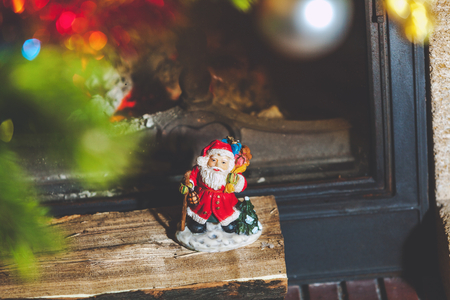Wooden log lies in front of the glass door of a burning fireplace. On logs is a Santa Claus figurine  Banque d'images