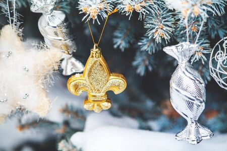 Group of Christmas toys of silver and yellow weigh on green branches snow-covered Christmas tree closeup  Stock Photo