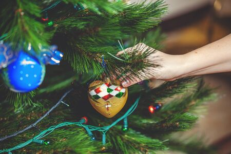 decorate: Decorate the Christmas tree. Womans hand hangs a beautiful toy in the shape of a heart on green coniferous branch close-up  Stock Photo