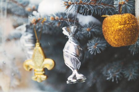 weighs: Group of Christmas toys of silver and yellow weigh on green branches snow-covered Christmas tree closeup  Stock Photo