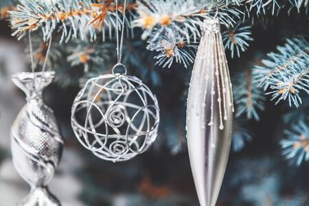 Group of Christmas toys of silver and yellow weigh on green branches snow-covered Christmas tree closeup