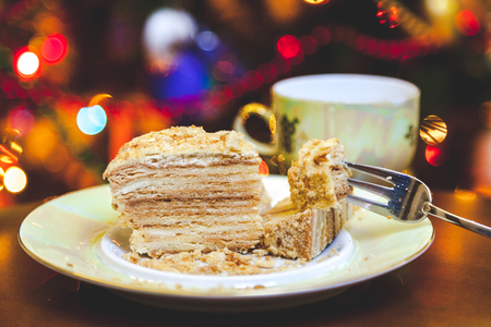 flashlights: delicious piece of cake is on the plate closeup. In the background, a tea cup and blurred the bright lights of a Christmas garland