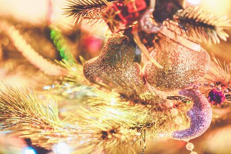 weighs: Christmas bells weighs on green fir branch close-up. Around the beautiful lights and blurred lights  Stock Photo