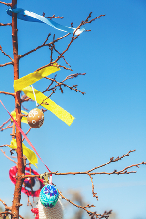 sanctified: several painted Easter eggs hanging on a tree branch against a blue sky