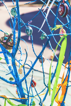 sanctified: Several Easter colored eggs hanging on a tree branch color sunny spring day