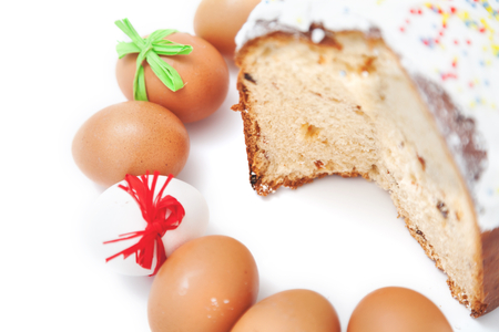 consecrated: Painted Easter eggs lie in a circle next to the sliced ??cake on a white background
