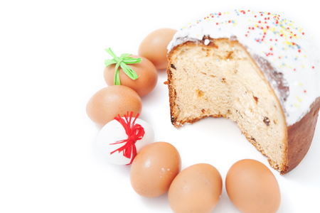 Painted Easter eggs lie in a circle next to the sliced ??cake on a white background