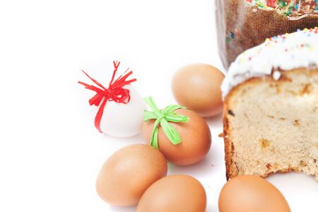 One cut and one whole Easter cake and six eggs with festive ribbons on a white background