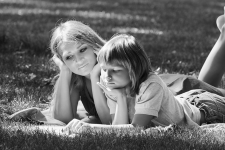 cohesive: Family fun on the grass. Beautiful mother and son lie on the grass near a sunny summer day, a monochrome image  Stock Photo
