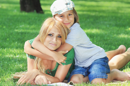 cohesive: Family harmony. Beautiful mother with her son in fashionable stylish cap lying on a green grassy lawn in a summer park