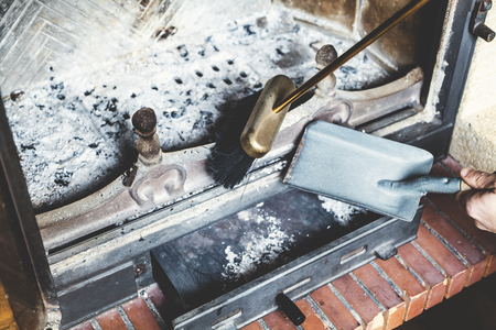 Cleaning the fireplace with an open tray brass brush and shovel