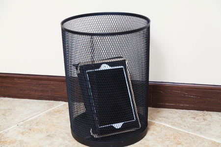 Discarded personal tablet computer is in an empty wastebasket