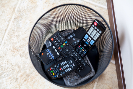 several remote controls of different shapes dumped in wastebasket