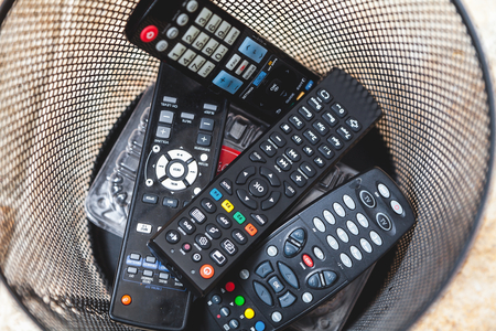 several panels of different forms of remote control are dumped into the waste-paper basket closeup  Stock Photo