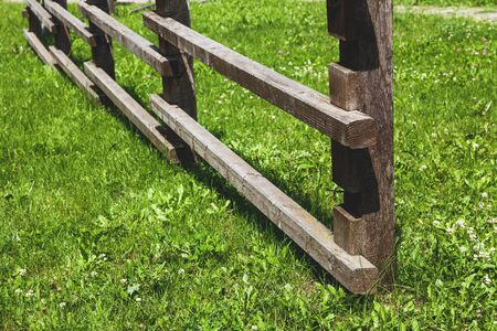 demarcation: Wooden fence of square bars on green grass lawn