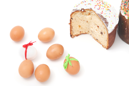 sanctified: Cut Easter cake and painted eggs with a few ribbons on a white background