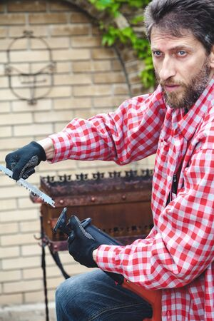 man with a beard in a red plaid shirt inserts in power saw sawing in the yard of a private house