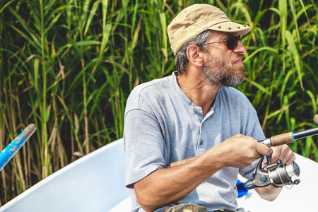 man with a beard wearing glasses fishing with a rowing boat with the help of spinning rod  Stock Photo