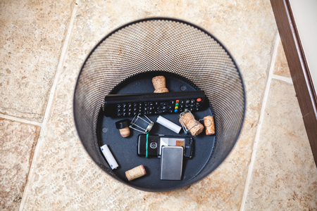 Remote control, a broken cell phone, wine stoppers, batteries are on the bottom of the wastebasket