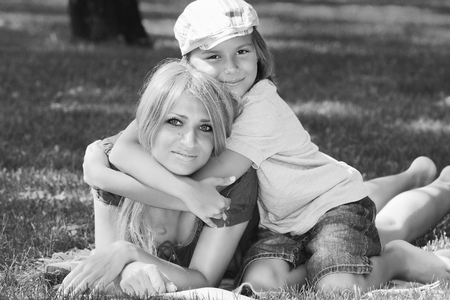 Family harmony. Beautiful mother with her son in fashionable stylish cap lying on a green grassy lawn in a summer park monochrome image