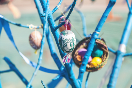 sanctified: Painted Easter egg hanging on a tree branch blue outdoors