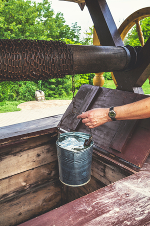 male hand pulls out pail filled with water from wooden well