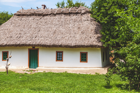 Beautiful white house in Ukrainian style thatched sunny summer day