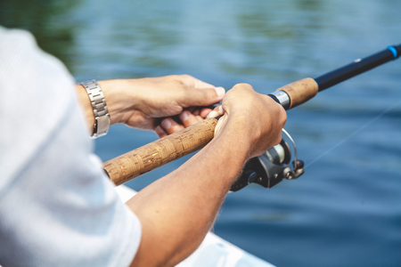 Hands fisherman keep spinning rod and rotate the handle fast-response spool close-up Banco de Imagens