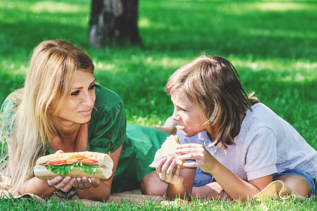 Family breakfast on the green lawn. Beautiful mother and son eating a sandwich fashion on a grassy meadow summer day Stock Photo
