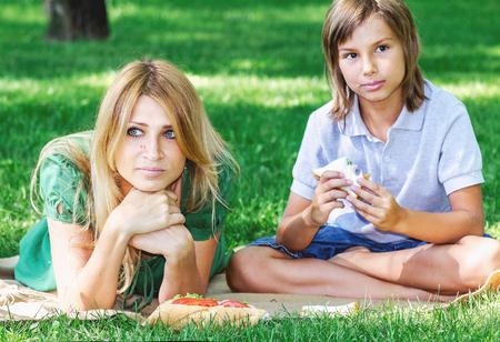 Prima colazione familiare sul prato verde. Bella madre e figlio mangiare una moda sandwich in un giorno di estate prato erboso Archivio Fotografico - 78199771
